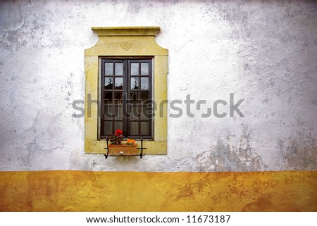 Old neglected house wall with flowery window - stock photo