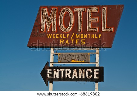 Old neon motel sign advertising monthly and weekly rates also shows if there is a vacancy and where the entrance is - stock photo