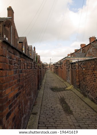 Old Northern British Cobbled Street Alleyway with Garden Walls - stock photo