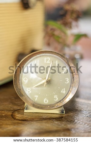 old nostalgic alarm on a table, Retro alarm clock on a table. Photo in retro color image style, vintage style - stock photo