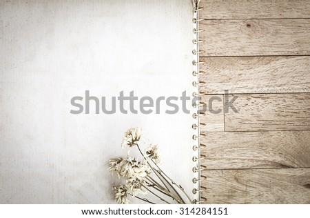 Old note book and dry flower on wood table with fade tone soft light and vignetting, space for text - stock photo