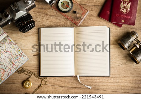 Old notebook, compass, map, vintage binoculars, photo camera on wooden background - stock photo