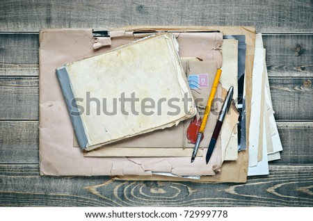 old notebook, envelope with paper and pens on a wooden table - stock photo
