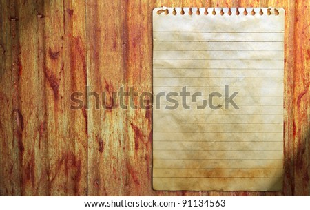 Old notebook paper on wall background - stock photo