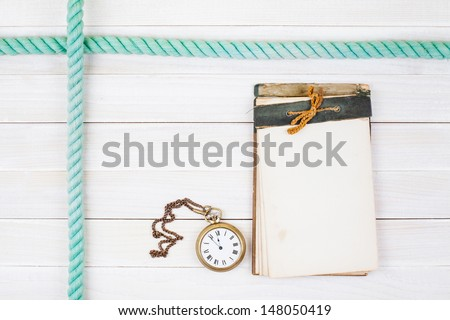 Old notebook, pocket watches, rope on white wood background - stock photo