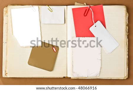 Old notebook with labels and photo frames inside over brown paper background - stock photo
