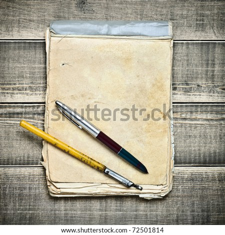 old notebook with pen on a wooden table - stock photo