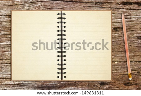old notebook with pencil on ancient wooden table background