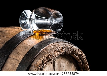 Old oak barrel and a glass of cognac - stock photo