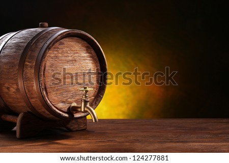 Old oak barrel on a wooden table. Behind blurred dark background. - stock photo
