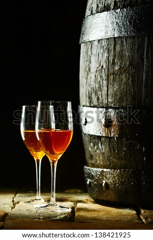 Old oak wine barrel with two glasses of sherry against a dark background reminiscent of a cellar in a winery - stock photo