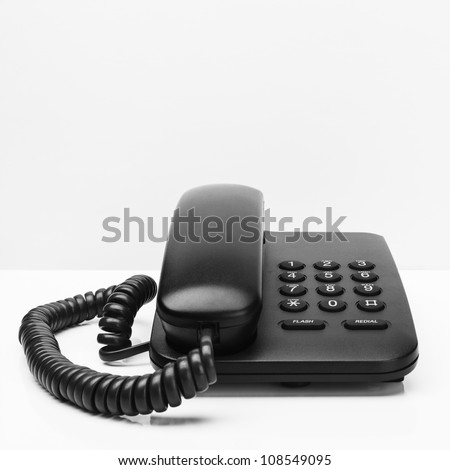 Old office desktop phone on white desk - stock photo