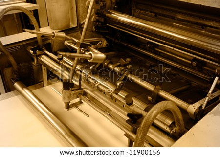 Old offset press machine in printing house - stock photo