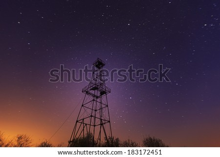 Old oil and gas rig structure, profiled on night sky, with star trails - stock photo