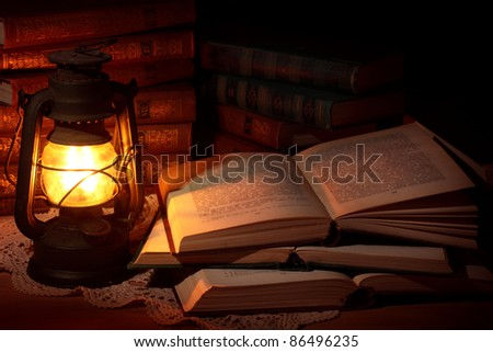 Old oil lamp and old books - stock photo