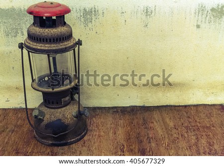 Old oil lamp on dark background ,processed in vintage style - stock photo