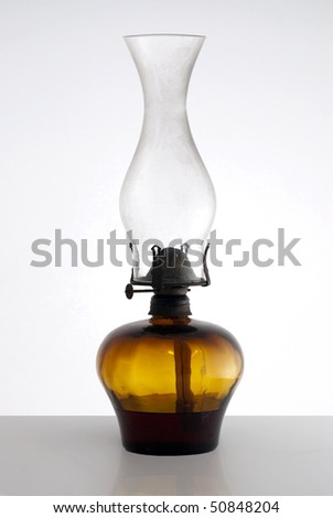 Old oil lamp on top of a table.