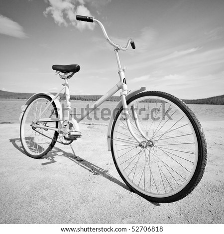 Old old-fashioned bicycle on the beach - a monochrome picture - stock photo