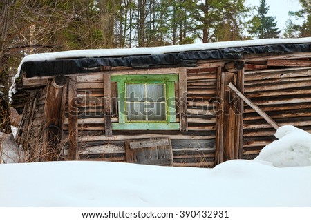 Old one-storey wooden house in the winter, Russia