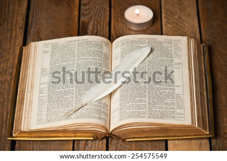 old open Bible and candle - stock photo