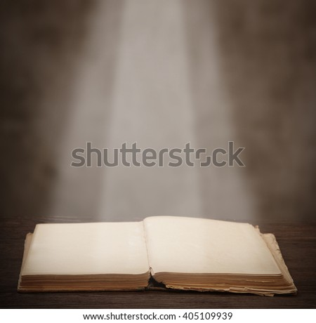 old open book lying on a wooden table light beam illuminates the page