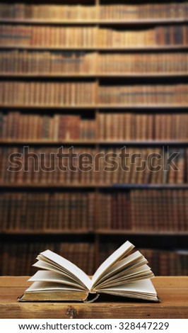 old open book on desk in a library. - stock photo