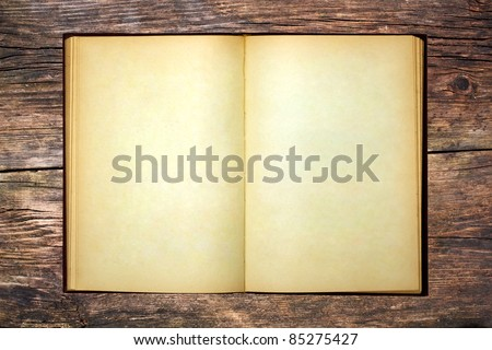 Old open book on wooden table - stock photo