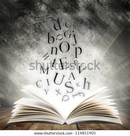 Old open book with magic light and falling letters on wood planks and dark abstract background - stock photo