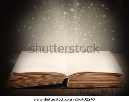 Old open book with magic light and falling stars on dark abstract background