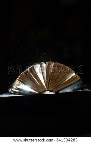old open book with the expanding dust around - stock photo