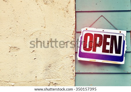Old open sign hanging on wood background.Retro color style. - stock photo
