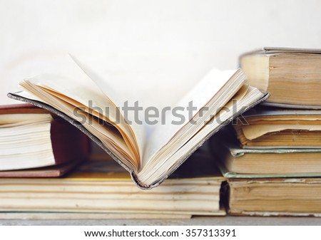 Old opened book at stack of books Selective focus - stock photo