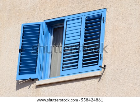 Old opened window and shutters painted with blue color, traditional Cyprus mediterranean style