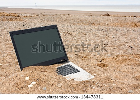 old or obsolete unwanted laptop on the beach with blank screen for your own message good concept for unwanted technology or travel websites - stock photo