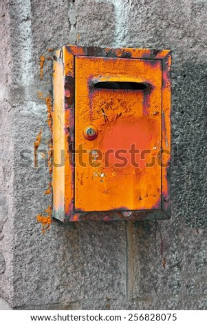 Old orange iron mailbox on stone wall. - stock photo