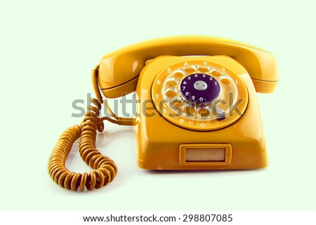 old Orange telephone with rotary dial color toned - stock photo
