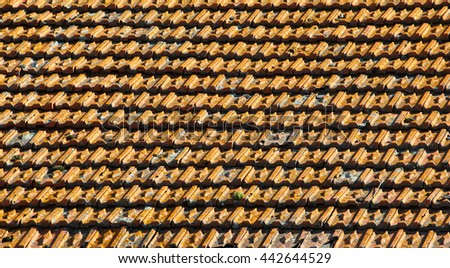 Old orange weathered roof shingles. Dirty stained ceramic tiles texture. - stock photo