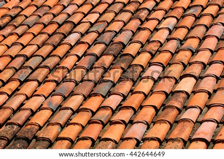 Old orange weathered roof shingles. Dirty stained ceramic tiles texture closeup. - stock photo