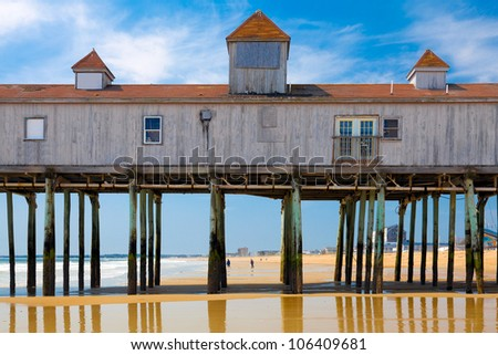Old Orchard Beach, Maine, historic wooden pier on the sand with reflections - stock photo