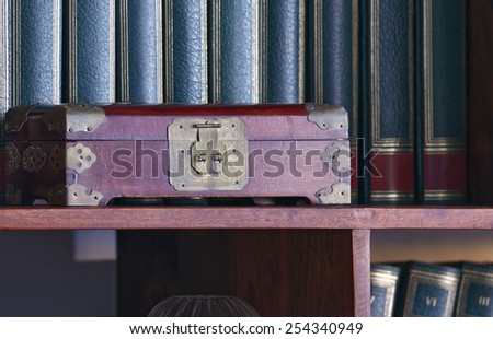 Old oriental hand made wooden box in a library - stock photo