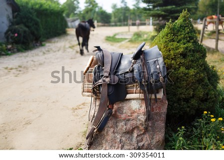 Old ornamental saddle on the stone outdoor at the summer time - stock photo