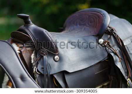 Old ornamental saddle on the wooden fence at summer time - stock photo