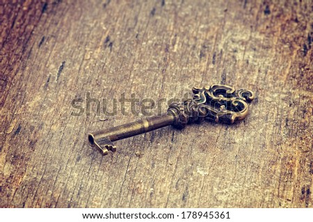 Old ornate skeleton key on rough wood background with retro filter effect  - stock photo