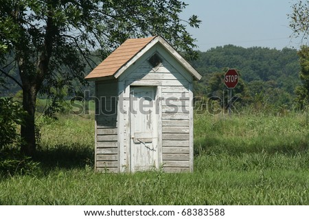 """Old outhouse under the tree with a stop sign in the background seemingly reminding passers by that now might be a good time for a """"pit"""" stop. - stock photo"""