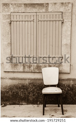 Old padded white leather chair standing near the window with closed wooden shutters outside of  the old house with stucco wall. Provence, France. Aged photo. Sepia. - stock photo