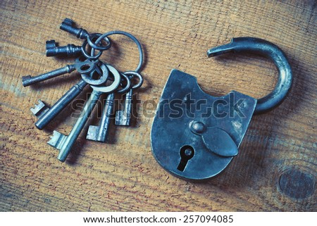 Old padlock and a bunch of keys on a wooden board - stock photo