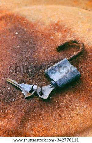 Old padlock and keys on rusty background, selective focus