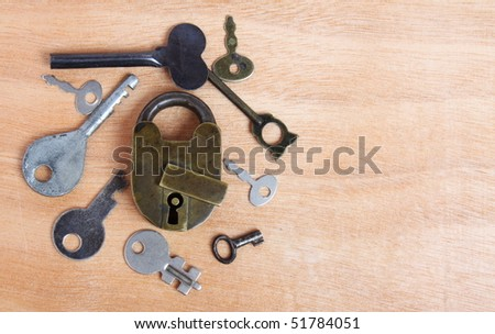 Old padlock and keys on wooden background - stock photo