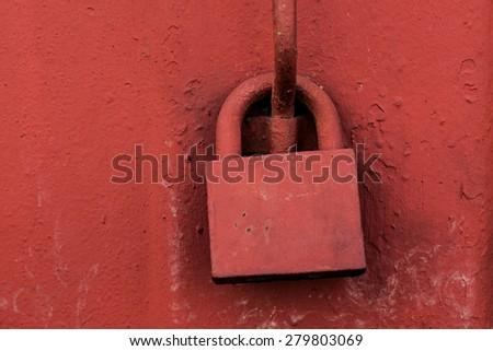 Old padlock on metal red door. - stock photo