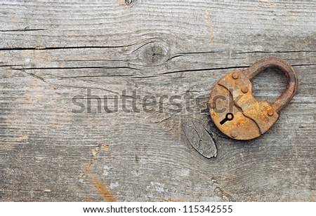Old padlock over wooden background.With copy space - stock photo